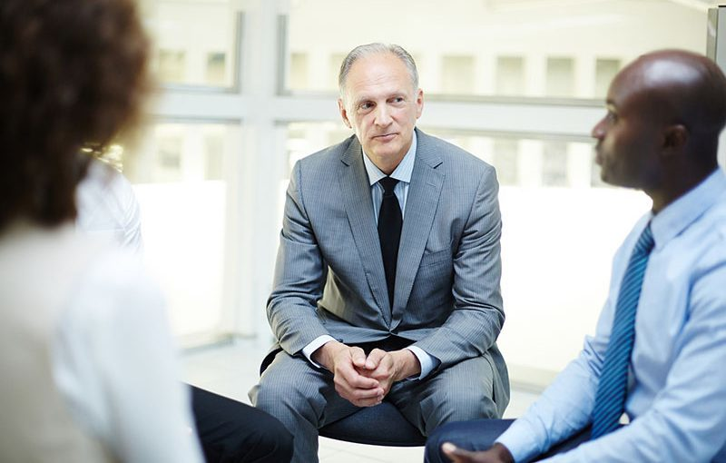 Attentive mature businessman listening to one of subordinates at