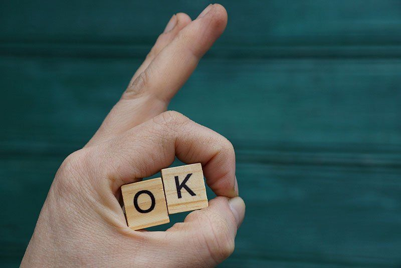 Hand Gesture And Wooden Letters With The Word Ok On A Green Back
